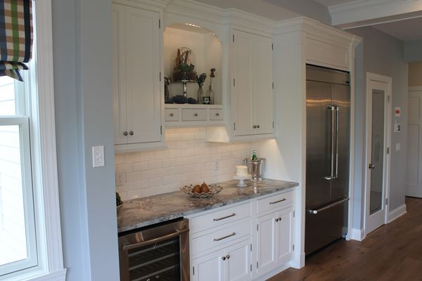 white cabinets with stainless steel refridgerator